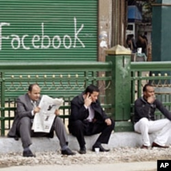 "Anti-government protesters sit next to a ""Facebook"" graffiti sign during demonstrations inside Tahrir Square in Cairo (File)"