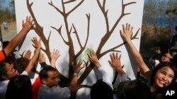 Ambientalistas hicieron simbólicas impresiones de las manos en una pared con la imagen de un árbol para conmemorar el Día de la Tierra el viernes, 22 de abril de 2016, en un suburbio al sur de Manila, Filipinas.