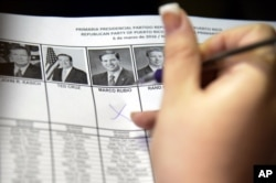A woman marks her vote for Florida's Senator Marco Rubio during Puerto Rico's Republican primary in San Juan, Puerto Rico, March 6, 2016.