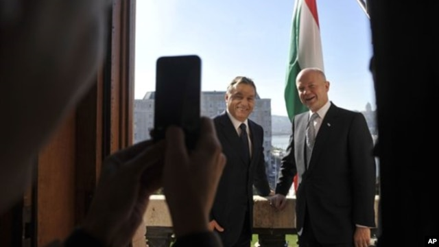 British Foreign Minister William Hague (L) and Hungarian Prime Minister Viktor Orban pose for photographers on a balcony during their meeting at Orban's office in the Parliament building in Budapest, Hungary, October 4, 2012.
