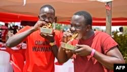 Les hommes mangent une Rolex lors du festival de Kampala Rolex à Kampala, le 19 août 2018.