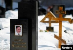 FILE - A picture of lawyer Sergei Magnitsky is seen on his grave in the Preobrazhensky cemetery in Moscow, March 11, 2013.