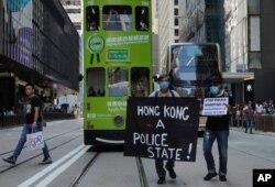 Para pengunjuk rasa memegang spanduk dalam peringatan 'flash mob' untuk mengenang Chow Tsz-Lok, mahasiswa yang tewas saat berunjuk rasa di Hong Kong, Jumat, 8 November 2019.