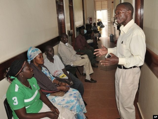 FILE - A health worker from The AIDS Support Organization (TASO) speaks with patients waiting for treatment in Kampala, Uganda, July 12, 2012.