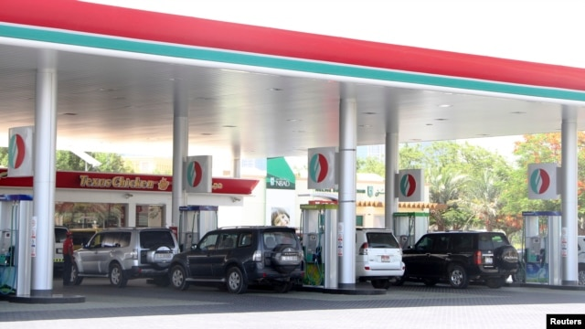 FILE - Cars queue for petrol at a gas station in Dubai, UAE, June 11, 2012. Saudi Arabia's planned cuts in spending and energy subsidies signal that the world's largest crude exporter is bracing for a prolonged period of low oil prices.