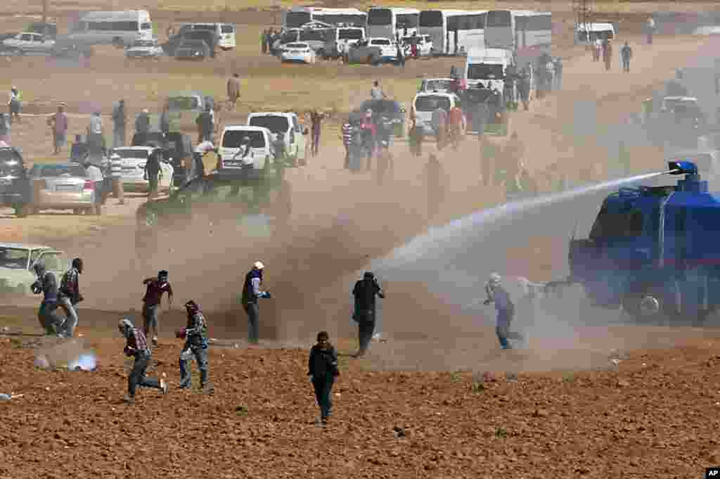 Riot police use water cannons to disperse Kurdish demonstrators who were clashing with Turkish security forces, as thousands of Syrian refugees continue to arrive at the border in Suruc, Turkey, Sept. 22, 2014.