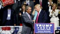 Kandidat presiden AS dari Partai Republik, Donald Trump, menyambut mantan pemimpin partai UKIP Inggris, Nigel Farage, dalam kampanye di Jackson, Mississippi (24/8). (AP/Gerald Herbert)