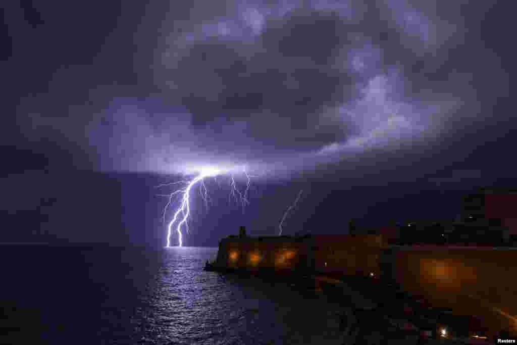 A lightning bolt strikes the sea near Fort St Elmo during a storm in Valletta, Malta, Feb. 27, 2019.