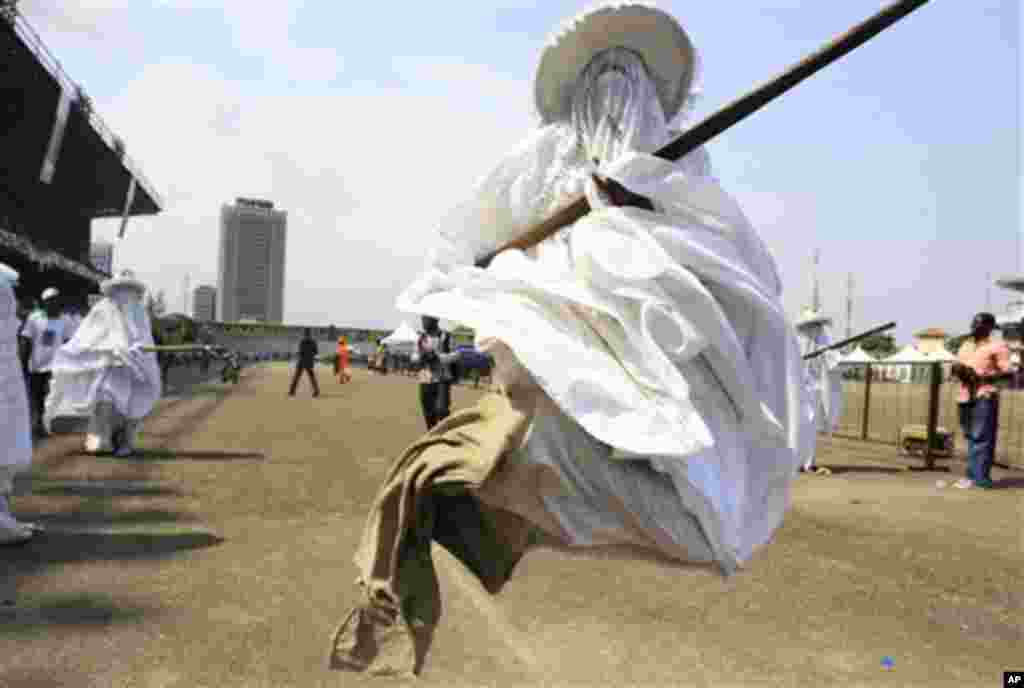 Eyo masquerades dance through Tafawa Balewa Square in Lagos, Nigeria, Saturday, Nov. 26, 2011, to honor the death of a prominent Lagos Chief Yusufu Abiodun Oniru. The shouting masquerades carry sticks and sometimes hit people who break traditional rules l
