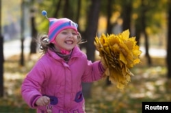 Kids all over the world like to play in the fallen leaves of autumn.