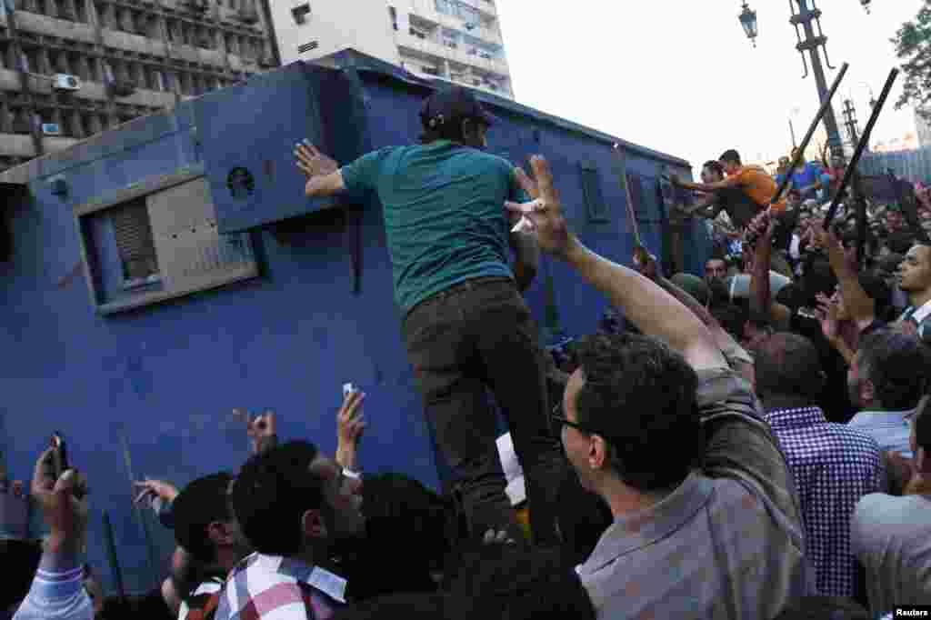 هواداران دولت موقت مصر - که توسط ارتش منصوب شده - در برابر خودروی پلیس که حامیان اخوان المسلمین را در مسجد الفتح قاهره بازداشت کرده و با خود می برد - بیست و ششم مرداد ۱۳۹۲