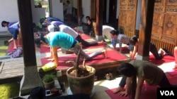 云南一家瑜伽会所的学员们正在练习流瑜伽。(美国之音朱诺拍摄,2015年10月8日)