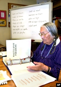In this file photo, Umatilla elder, the late Cecilia Bearchum goes over a large binder used to teach Walla Walla, a critically endangered language spoken at the Umatilla Indian Reservation, Ore., March 6, 2002. Ms. Bearcham passed away April 18, 2011 at
