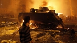 A protester watches as an Egyptian army vehicle burns in downtown Cairo on Friday