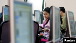 FILE - Vietnamese people work with computers at a media center in Hanoi.
