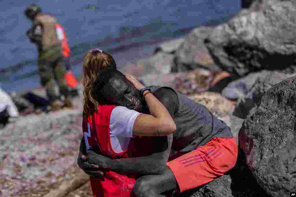 A migrant is comforted by a member of the Spanish Red Cross near the border of Morocco and Spain, at the Spanish enclave of Ceuta. Thousands of Moroccans took advantage of relaxed border control in their country to swim or paddle into European soil.