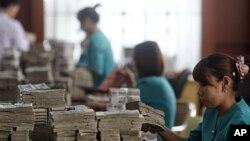 Nhân viên đếm tiền tại một ngân hàng địa phương ở Rangoon, Miến Ðiện