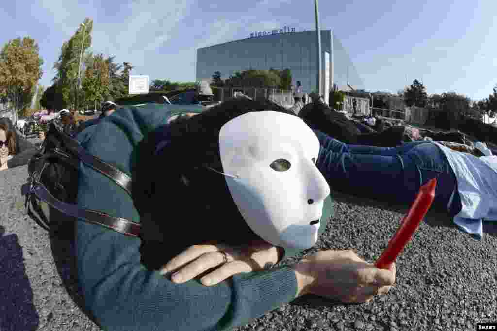 An employee at French newspaper Nice-Matin wears a mask and holds a candle as she lays on the road in front of their headquarters in Nice, as part of a demonstration by labor union members to symbolise the death of their jobs.
