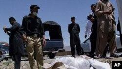 巴基斯坦保安官员4月29日站在遇害的英国医生哈利勒.戴尔的尸体旁
