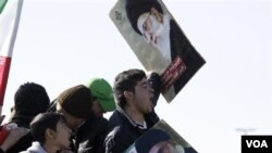 Para remaja Iran ikut meramaikan perayaan HUT Revolusi Islam sambil membawa poster Ayatollah Ali Khamenei di Teheran (11/2).