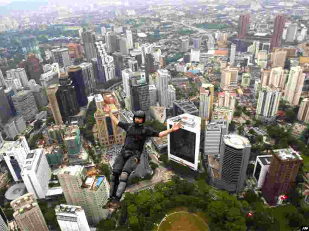 BASE jumper Walter Hilscher of Germany leaps from Kuala Lumpur Tower during the KL Tower International Jump in Kuala Lumpur, Malaysia, Thursday, Oct. 7, 2010. BASE stands for the places such jumpers usually leap from: buildings, antennae, spans and earth.