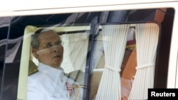 FILE - Thailand's King Bhumibol Adulyadej sits in a vehicle as he leaves Siriraj Hospital for the Grand Palace to join a ceremony marking Coronation Day in Bangkok, May 5, 2015.