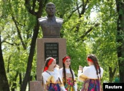 FILE - Girls react during the unveiling of a bust of Soviet dictator Joseph Stalin in the village of Trunovskoye in Stavropol region, Russia, May 5, 2017. A recent poll has found that 77 percent of respondents aged 18-24 years support similar Stalin memorials.