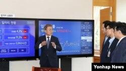 문재인(왼쪽) 대통령이 24일 오전 청와대 여민관 집무실에 설치한 일자리 상황판 모니터를 보며 참모들에게 고용 현황을 설명하고 있다.