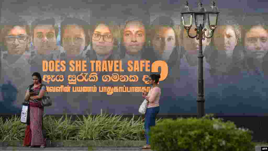 Women stand near a banner of an International Women's Day photo show in Colombo, Sri Lanka, ahead of International Women's Day, which is celebrated every year on March 8.