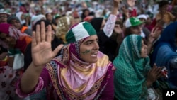 A supporter of Tahir ul-Qadri, Sufi cleric and leader of political party Pakistan Awami Tehreek (PAT) ,reacts as she listens to her leader's speech in front of the Parliament house building during the Revolution March in Islamabad, Aug. 28, 2014.