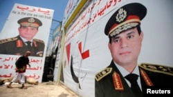 Ông Salah Abdel Moneim một người ủng hộ quân đội chống cựu tổng thống Morsi dán các tấm áp phích hình của Tổng tư lệnh Quân đội Ai Cập Abdel Fattah al Sissi, trước cửa tiệm của ông trong thủ đô Cairo, 7/8/13