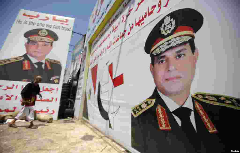Salah Abdel Moneim, an anti-Morsi supporter of Egypt's army, walks in front of his shop, plastered with huge posters of Egypt's army chief General Abdel Fattah al-Sisi, Cairo, August 7, 2013.