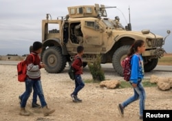 FILE - Syrian schoolchildren walk as U.S. troops patrol near the Turkish border in Hasakah, Syria, Nov. 4, 2018.