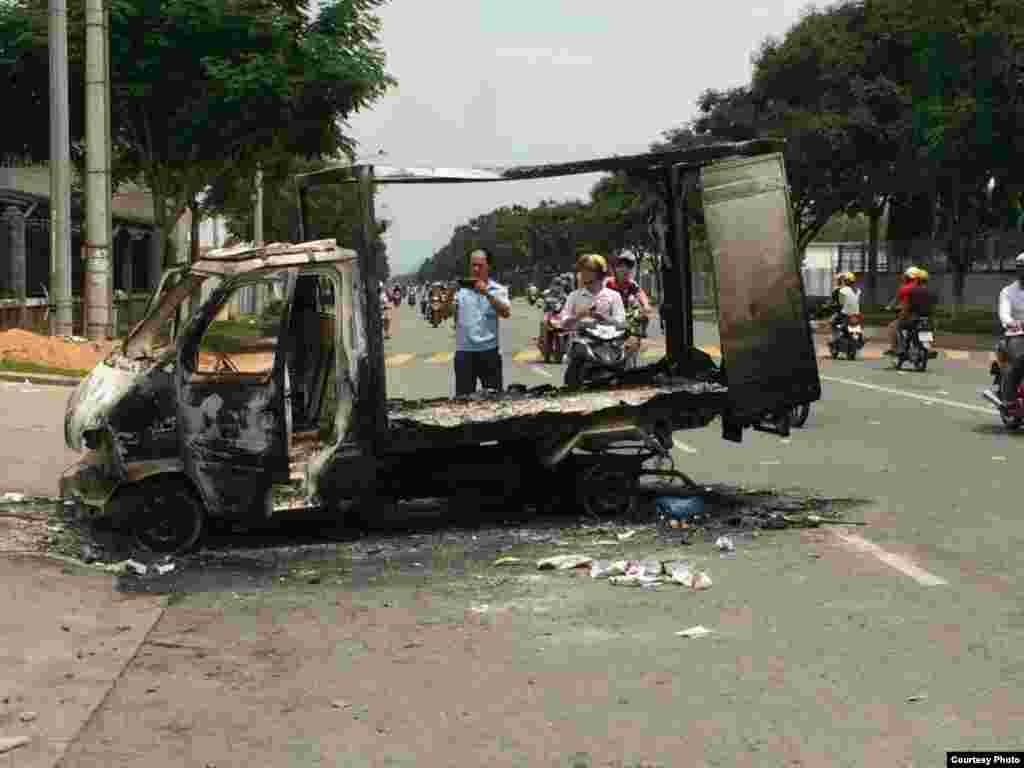Passersby photograph a burned out vehicle after angry mobs burned and looted scores of foreign-owned factories in Binh Duong province, Vietnam.