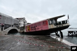 A stranded ferry boat lies on its side, in Venice, Wednesday, Nov. 13, 2019.
