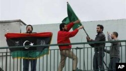 Libyans who live in Greece remove the Libyan flag from a Libyan state school as another shouts slogans and holds the old flag of his country during a protest in Athens, Tuesday, Feb. 22, 2011. About 60 Libyans gathered at the protest against Gadhafi's cra