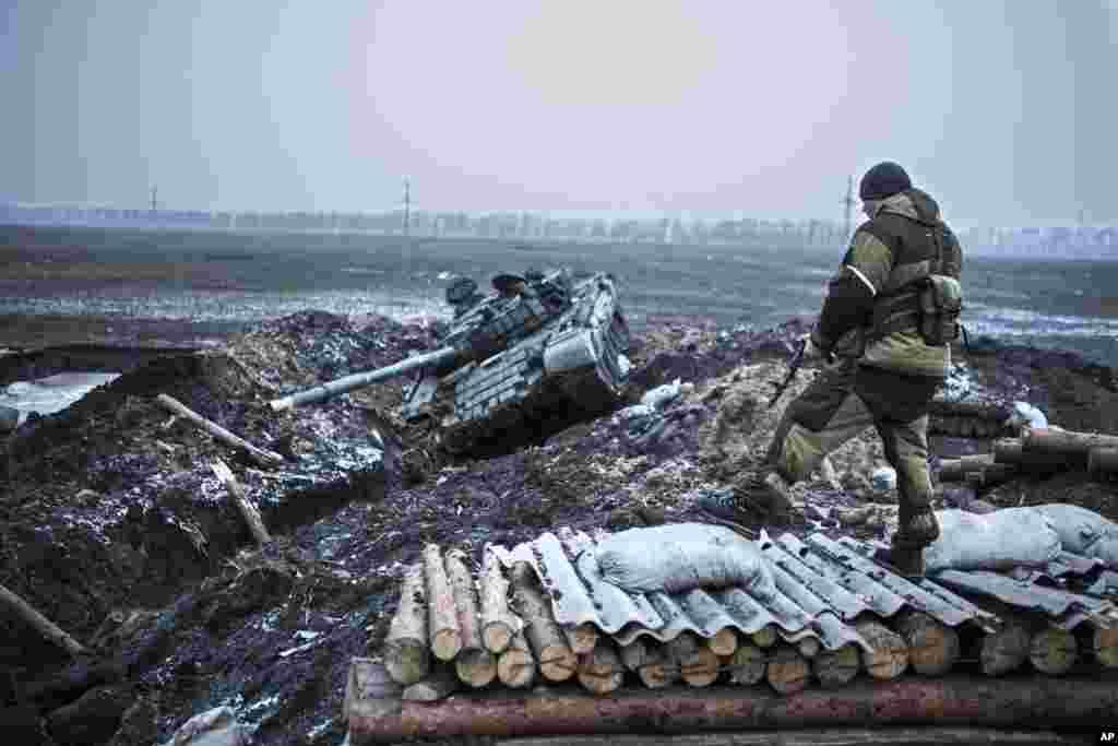 A pro-Russian rebel guards a captured former Ukrainian Army checkpoint outside Vuhlehirsk, Donetsk region, eastern Ukraine, Feb. 5, 2015.