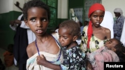 Somali girls carry their malnourished siblings in Banadir hospital, south of capital Mogadishu, August 28, 2011.