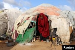 A Somali woman walks out from her makeshift shelter at a camp for the internally displaced people outside Mogadishu, Somalia August 28, 2018.