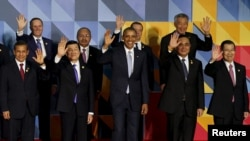 "U.S. President Barack Obama (C) and other leaders of the 21-member Asia-Pacific Economic Cooperation (APEC) summit wave to the media after an official ""family photo"" in Manila, Nov. 19, 2015."