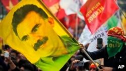 ຊາວໜຸ່ມຄົນນຶ່ງ ຖືທຸງພ້ອມກັບຮູບຂອງທ້າວ ອັບດຸລລາ ໂອກາລານ, ຜູ້ນຳກຸ່ມກະບົດຊາວ ເຄີດ ທີ່ຖືກຂັງຄຸກ ຈາກພັກກຳມະກອນຊາວ ເຄີດ ຫຼື PKK, ໃນນະຄອນ ອິສຕັນບູລ, ປະເທດ ເທີກີ. 21 ມີນາ, 2018.