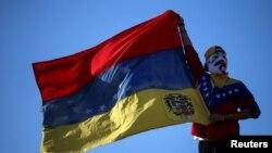 Un manifestante enmascarado ondea una bandera de Venezuela durante una protesta en favor del opositor Juan Guaidó, en Buenos Aires, el 2 de febrero de 2019.
