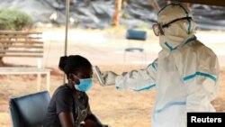 Vérification des températures lors du confinement national pour aider à freiner la propagation du coronavirus, dans un centre de dépistage à Harare, Zimbabwe, le 30 avril 2020.