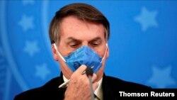 FILE PHOTO: Brazil's President Jair Bolsonaro adjusts his protective face mask at a press statement during the coronavirus disease (COVID-19) outbreak in Brasilia