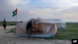 Palestinians set up tents in preparation for mass demonstrations along the Gaza strip border with Israel, in eastern Gaza City, Tuesday, March 27, 2018. (AP Photo/Adel Hana)