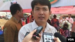 Ung Vuthy, local coordinator for CЕDAC, is seen being interviewed by reporters at the community market in Kompong Speu province. (Photo - Hul Reaksmey/VOA Khmer)