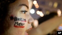 "FILE - A woman with ""Black Lives Matter"" written across her cheek attends an ATlanta demonstration against the deaths of unarmed black men at the hands of white police officers."
