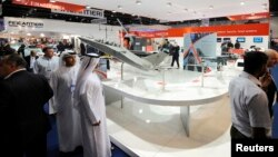 Visitors walk past a stand for Italian defence group Finmeccanica during the International Defense Exhibition and Conference (IDEX) at the Abu Dhabi National Exhibition Centre, February 19, 2013.
