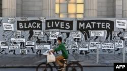 """Seorang pengendara sepeda melewati mural """"Black Lives Matter"""" di Union Square pada 12 Juni 2020 di New York City. Demonstrasi diadakan di seluruh AS setelah kematian George Floyd pada 25 Mei 2020. (Foto: AFP)"""