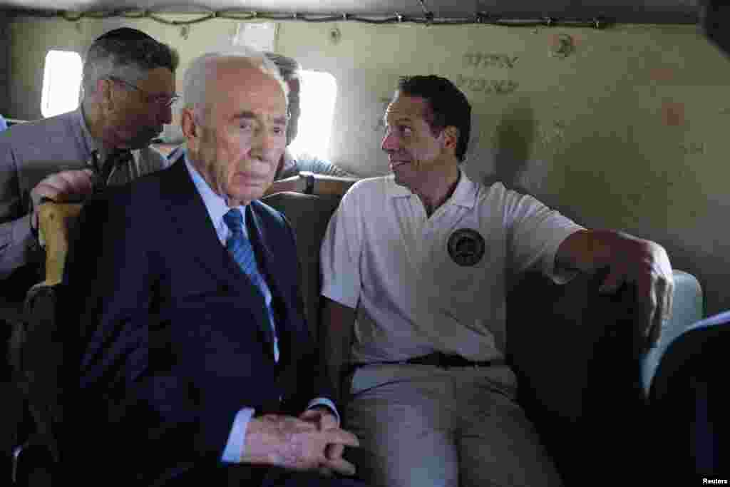 Former Israeli President Shimon Peres (second from left) and New York Governor Andrew Cuomo, right ride an armored vehicle during a tour near the border with the Gaza Strip, Aug. 14, 2014.